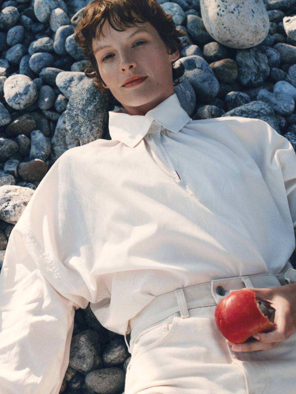 Female model in white shirt and white trousers laying down on a nordic pebble beach holding an apple