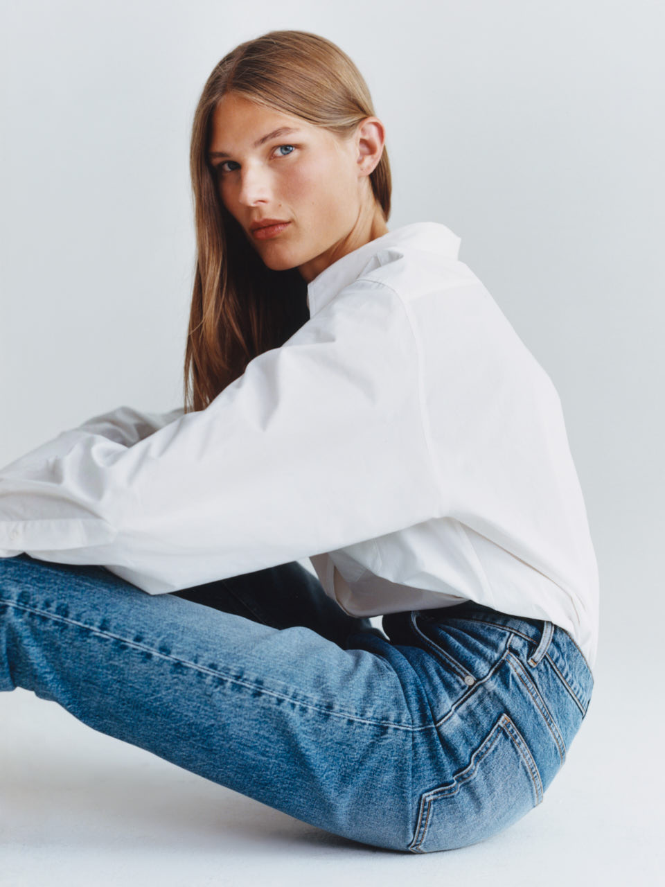 Female model wearing white shirt and blue jeans