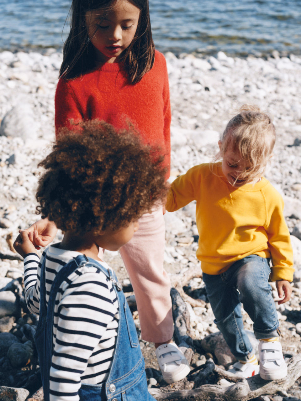 Chiildren wearing basics in vivid colors playing on a pebble beach