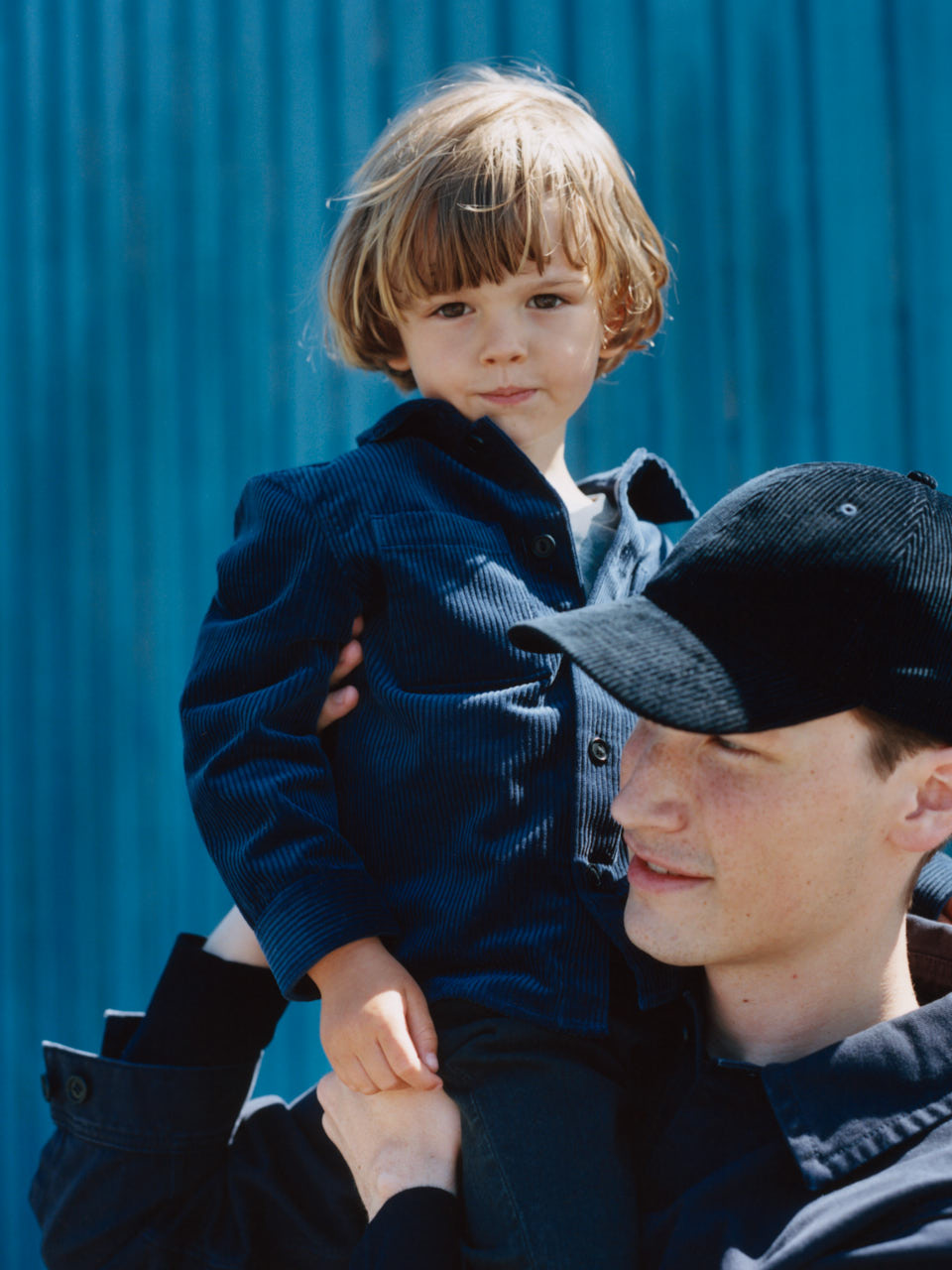 Male model with a black corduroy cap on carrying a child model wearing a blue corduroy jacket