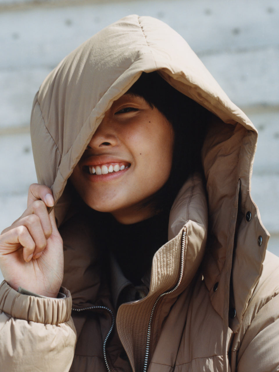 Female model smiling wearing an ARKET Upcycled Down jacket