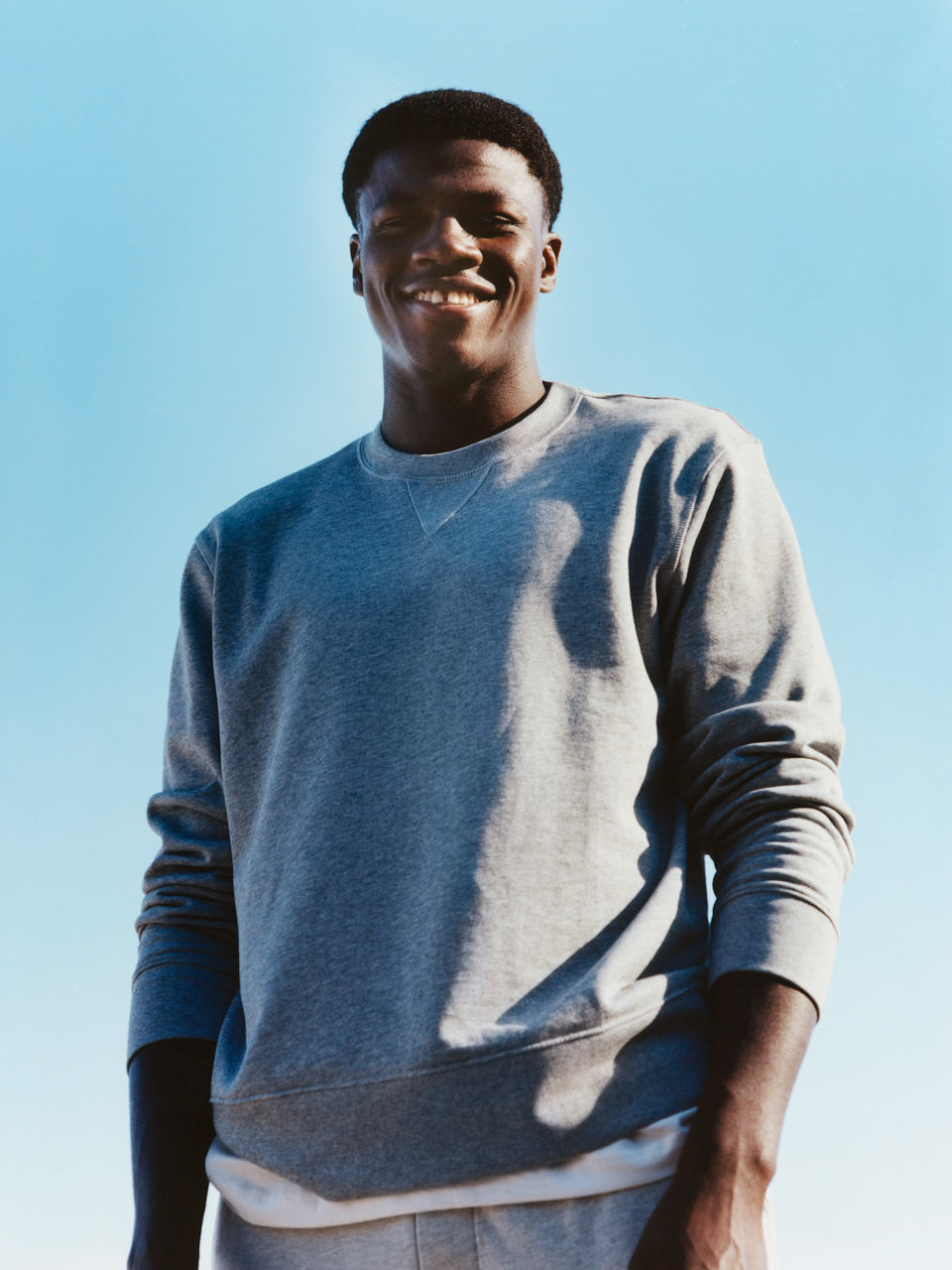 Male model smiling wearing a grey sweatshirt