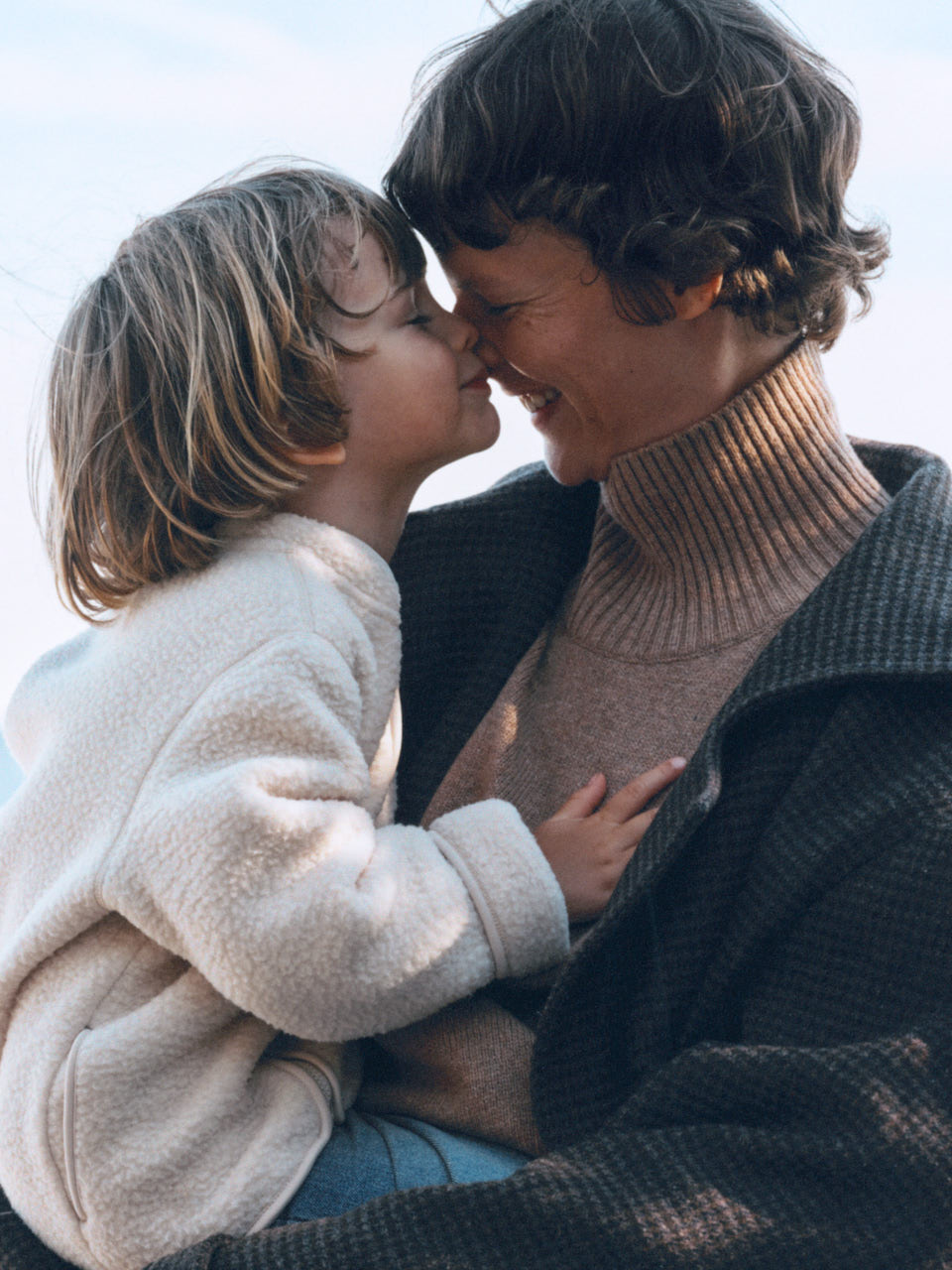Child model wearing a white pike jacket hugging a female model wearing a turtleneck and a jacket