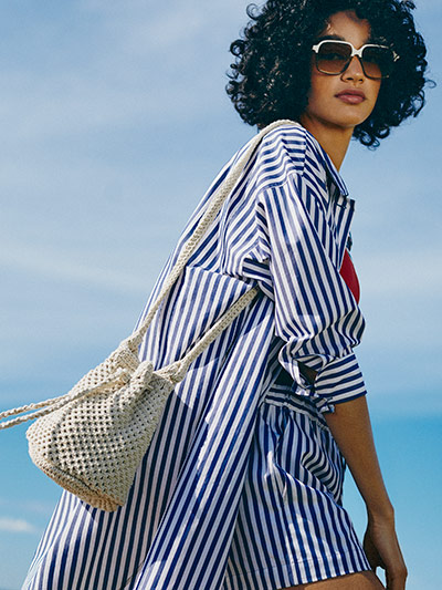cd4661f03 Woman wearing a stripe poplin shirt, a white crochet bucket bag and  sunglasses